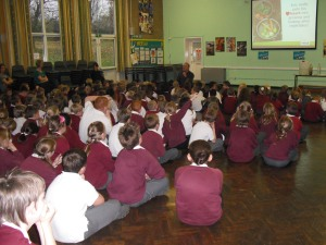 School Volunteer, Andy Ogley, leads assembly (on his knees!)